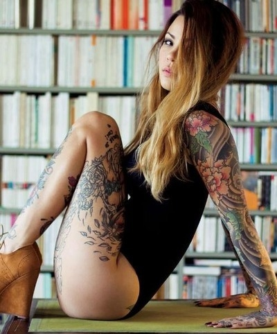 Young girl with amazing tattos sitting on the library