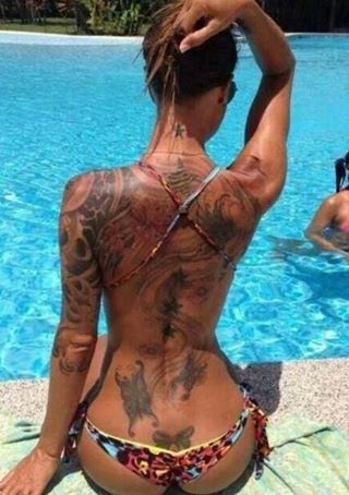 Tattoo babe at the pool has a round ass very tan girl