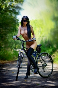 Hot boobs brunette with tattoos riding a bike in the park - Brunette